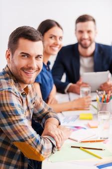 Wir sind die besten! drei fröhliche geschäftsleute in smarter freizeitkleidung sitzen zusammen am tisch und schauen in die kamera
