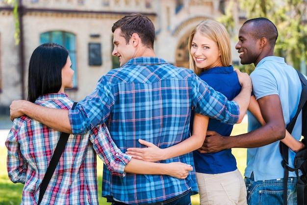 Wir sind die besten freunde! rückansicht einer schönen jungen frau, die über die schulter schaut und lächelt, während sie zusammen mit freunden spazieren geht