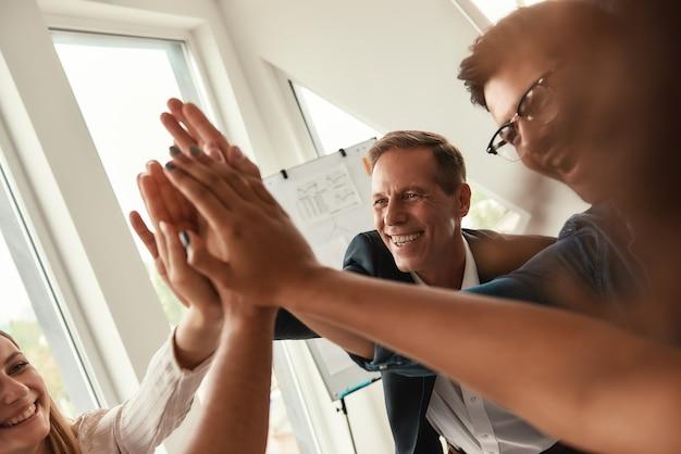 Wir sind die besten team-geschäftsleute, die sich gegenseitig highfive geben und während der arbeit lächeln