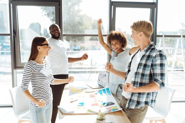 Wir sind die gewinner. überglücklich lächelnde junge kollegen, die im büro stehen und sich nach einem erfolgreichen projekt während der zusammenarbeit glücklich fühlen