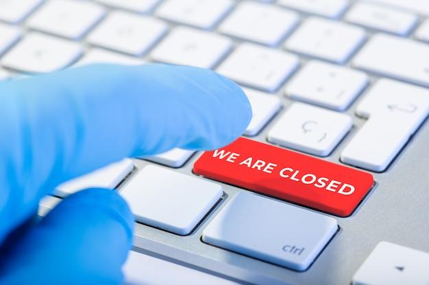 Wir sind geschlossenes konzept. hand mit schutzhandschuh und tastatur mit rotem schlüssel. coronavirus covid-19-ausbruchskonzept