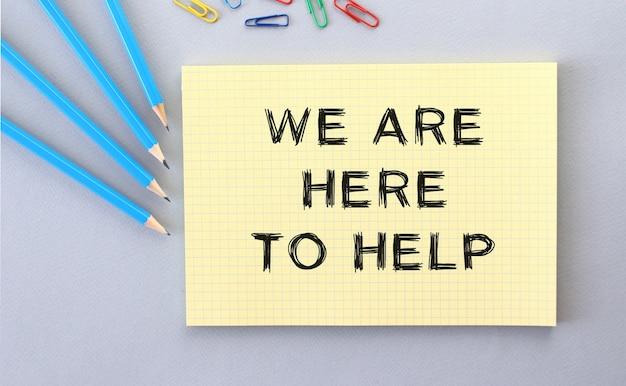 Wir sind hier, um text in notizbuch auf grauem hintergrund neben stiften und büroklammern zu helfen. konzept.