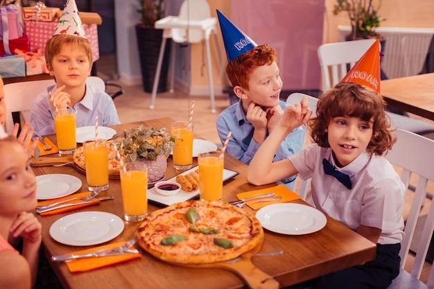 Wir sind hungrig. fröhlicher junge mit lockigen haaren, der ein lächeln auf seinem gesicht behält, während er einen papierhut trägt