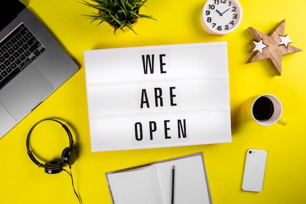 Wir sind offener text auf leuchtkasten auf modernem gelbem bürodesktop mit laptop
