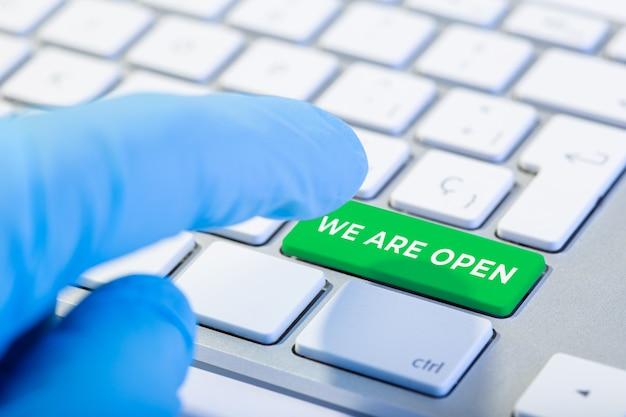 Wir sind offenes konzept. hand mit schutzhandschuh, der eine tastatur mit grüner taste tippt