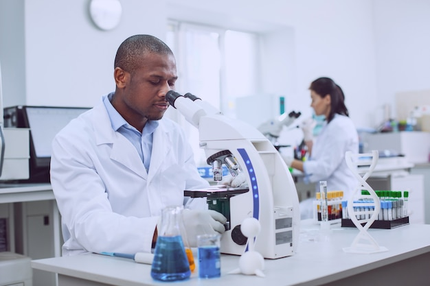 Wir sind profis. inspirierter professioneller biologe, der mit seinem mikroskop arbeitet, und sein mitarbeiter, der im hintergrund arbeitet