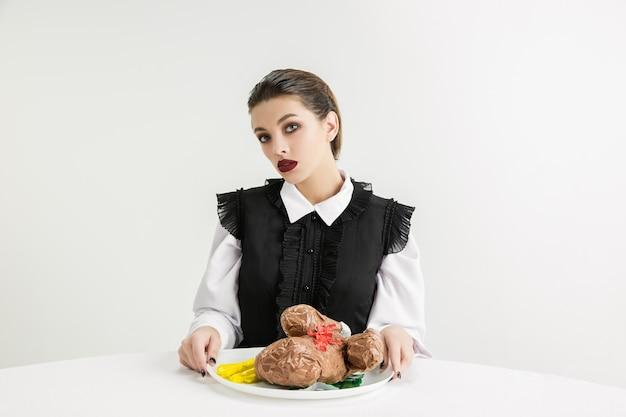 Wir sind was wir essen. frau isst brathähnchen aus kunststoff, öko-konzept