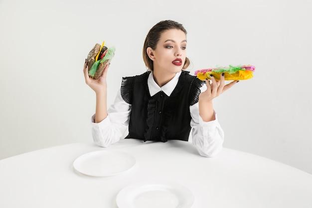 Wir sind was wir essen. frau isst burger und hot-dog aus kunststoff, öko-konzept. es gibt so viele polymere, dass wir einfach daraus gemacht sind. umweltkatastrophe, mode, schönheit, essen. bio verlieren.