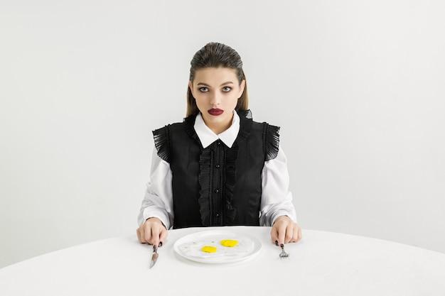 Wir sind was wir essen. frau isst spiegeleier aus kunststoff, öko-konzept. es gibt so viele polymere, dass wir einfach daraus gemacht sind. umweltkatastrophe, mode, schönheit, essen. die organische welt verlieren.