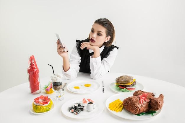 Wir sind was wir essen. frau mit smartphone gegen geschirr aus kunststoff, öko-konzept. ketchup, sushi, brathähnchen, burger. umweltkatastrophe, mode, schönheit, essen. die organische welt verlieren.