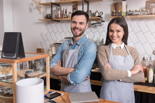 Wir sind zusammen stark. frohes junges paar, das die hände auf der brust kreuzt und lächelt, während es hinter der bar steht.