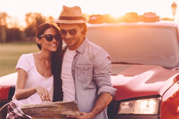 Wir sollten diesen ort sehen. schönes junges paar, das sich aneinander bindet und sich an ihren pick-up-truck lehnt, während es gemeinsam die karte untersucht