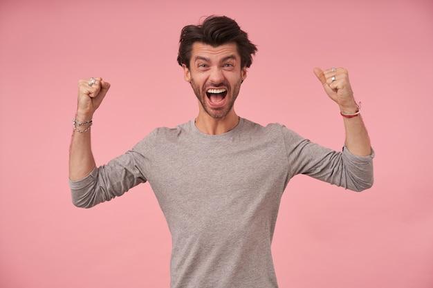 Wirbelnder junger hübscher mann mit trendigem haarschnitt, der glücklich die fäuste hebt, in freizeitkleidung steht, freudig schreit und die stirn runzelt