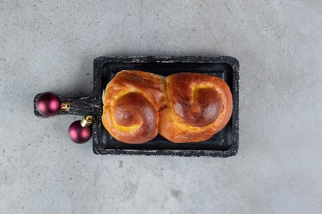 Wirbelndes süßes brötchen auf einem kleinen tablett auf marmortisch.