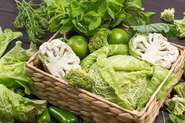 Wirsing, brokkoli und blumenkohl im rattankorb. hölzerner hintergrund. ansicht von oben