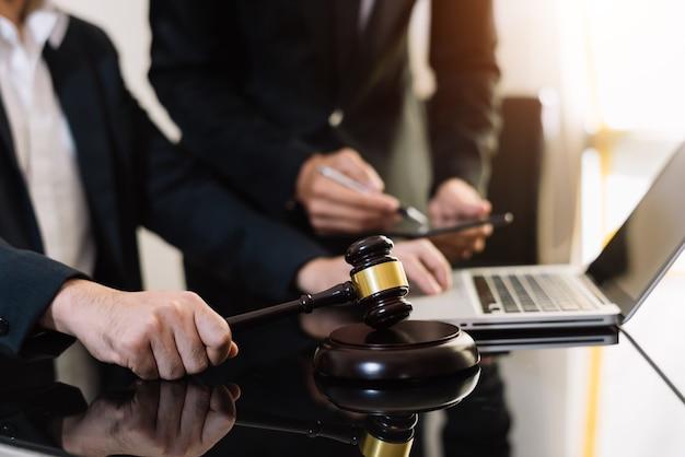 Wirtschaft und anwälte diskutieren vertragspapiere mit messingwaage auf dem schreibtisch im büro. recht, rechtsberatung, beratung, justiz und rechtskonzept.