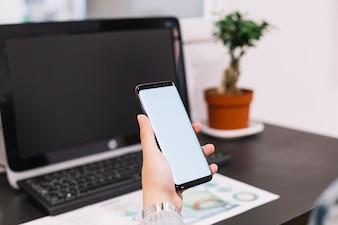 Wirtschaftler, der Smartphone mit leerem Bildschirm gegen den Desktop hält
