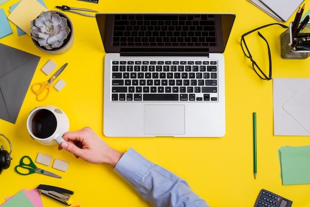 Wirtschaftler, der tasse kaffee und laptop über dem gelben hintergrund hält