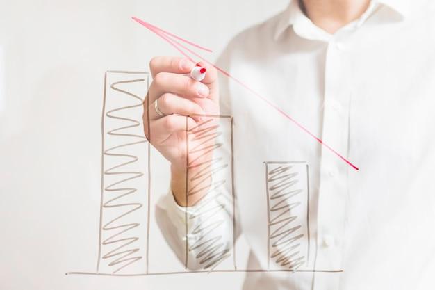 Wirtschaftler, der zunehmende diagramme mit rotem pfeil auf glasbrett zeigt
