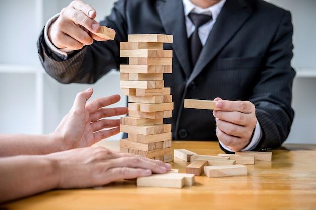 Wirtschaftler, die hölzernen block auf den turm, konzept des alternativen risikos setzen und ziehen