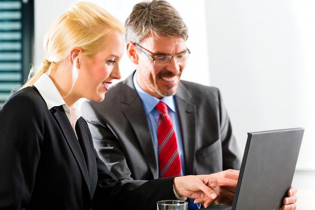 Wirtschaftler, die in absprache laptop betrachten