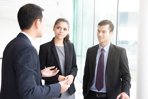 Wirtschaftler, die in der bürohaushalle sprechen