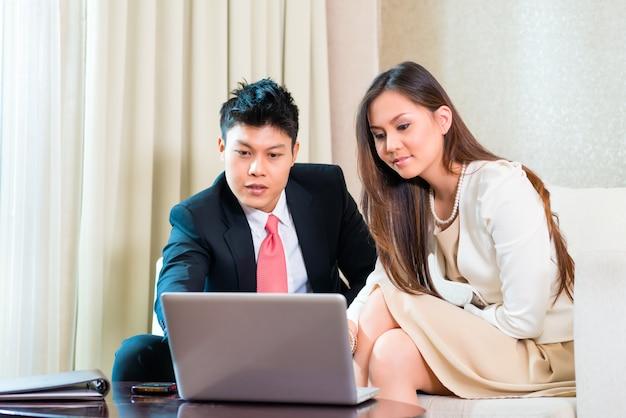 Wirtschaftler im asiatischen hotelzimmer mit laptop