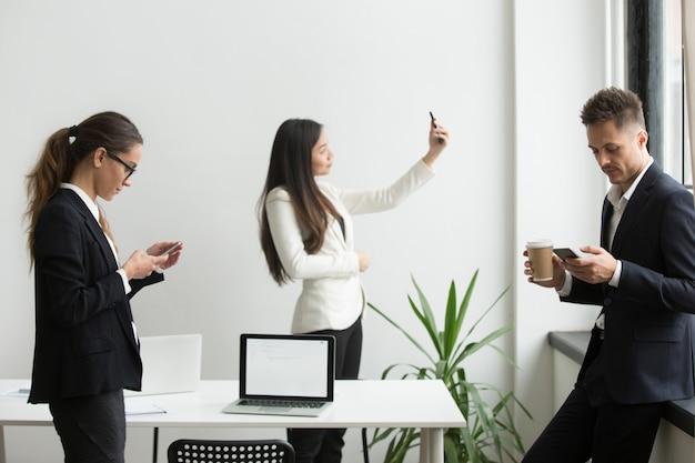 Wirtschaftler, welche die smartphones simsen, selfie im büro während des bruches nehmend verwenden