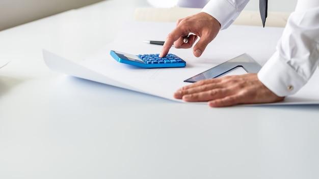 Wirtschaftsingenieur, der mit taschenrechner rechnet, während er an einem projekt mit lineal, bleistift und papier auf seinem schreibtisch arbeitet.