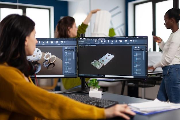 Wirtschaftsingenieurin, die am pc mit zwei monitoren arbeitet, auf denen cad-software angezeigt wird