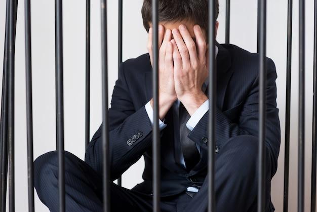 Wirtschaftskrimineller. depressiver junger mann in abendgarderobe, der hinter einer gefängniszelle steht