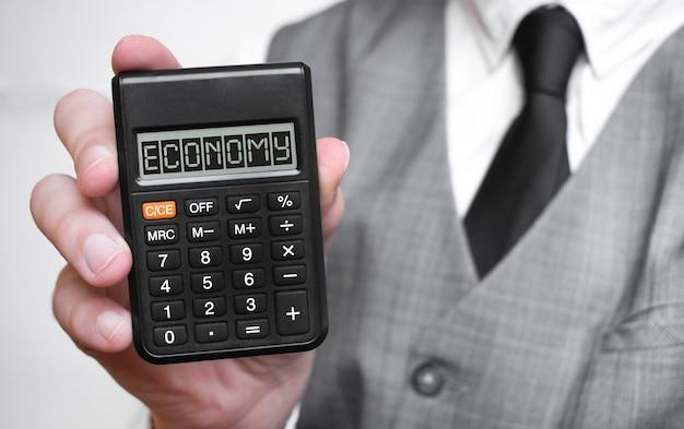 Wirtschaftstext-textinschrift auf taschenrechner in einer männlichen hand eines geschäftsmannes im weißen hemd und in der blauen krawatte