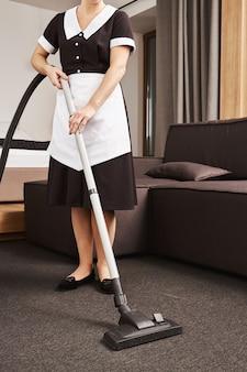 Wischen sie das chaos ab. horizontal beschnittener schuss des dienstmädchens im einheitlichen reinigungswohnzimmer des arbeitgebers mit staubsauger, staub entfernend und haus sauber und ordentlich halten, während familie im urlaub ist