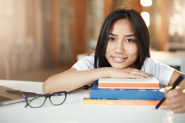 Wissen ist macht. junger asiatischer student, der kamera betrachtet, die nach einem harten tag in der universität ruht.
