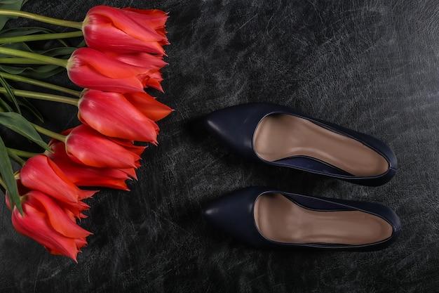 Wissen oder muttertag. rote tulpen mit schuhen mit hohen absätzen auf einer kreidetafel. ansicht von oben.