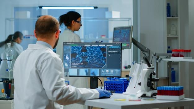Wissenschaftler arbeiten an der entwicklung eines neuen impfstoffs in einem modern ausgestatteten labor und tippen am computer. gruppe von biochemie-ärzten, die die virusentwicklung mit high-tech zur erforschung der behandlung untersuchen