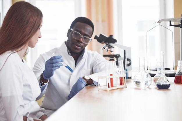 Wissenschaftler arbeiten im labor eng mit dem mikroskop zusammen, indem sie experimente und analysen durchführen.