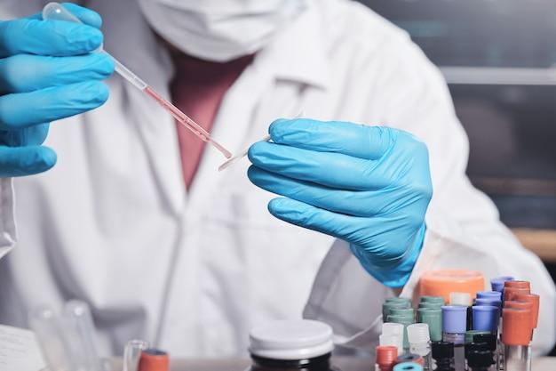 Wissenschaftler arbeiten in einem modernen labor und tragen einen tropfen flüssigkeit auf einen objektträger für ein mikroskop im medizinischen labor auf. medizinisches forscherkonzept.