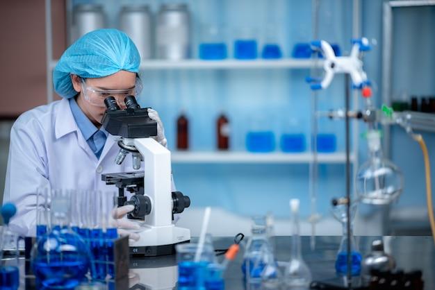 Wissenschaftler arbeiten mit mikroskop in labor, medizinische forschung