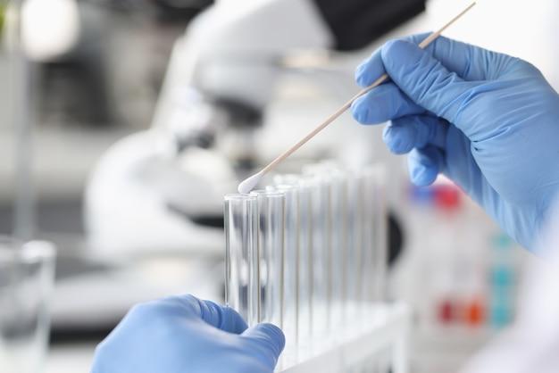Wissenschaftler chemiker, der wattestäbchen in glas reagenzglas nahaufnahme dna-untersuchungskonzept einführt