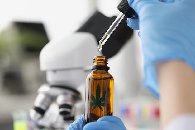 Wissenschaftler chemiker tropft marihuanaöl aus der pipette in das glas auf dem hintergrund des mikroskops