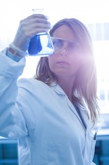 Wissenschaftler, der becher der chemikalie hält