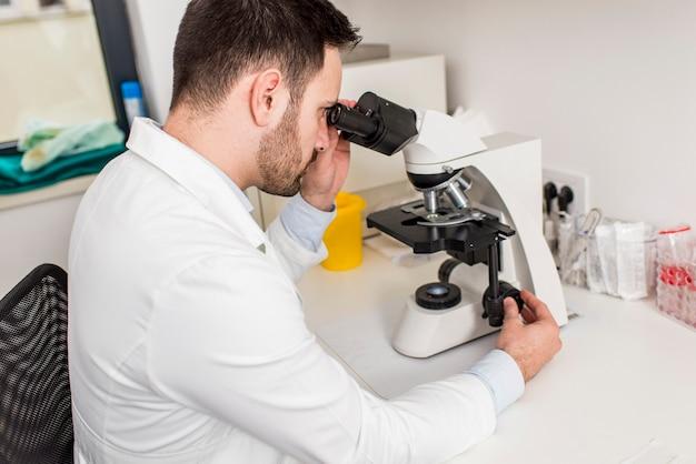 Wissenschaftler, der durch ein mikroskop in einem labor am krankenhaus schaut