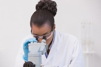 Wissenschaftler, der durch ein Mikroskop schaut
