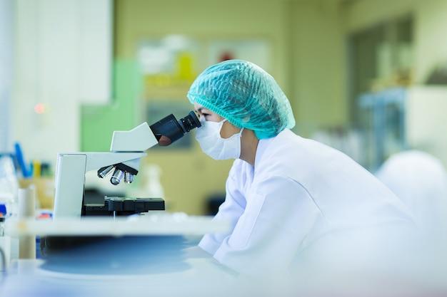 Wissenschaftler, der ein mikroskop in einem labor, in einer konzeptwissenschaft und in einer technologie verwendet