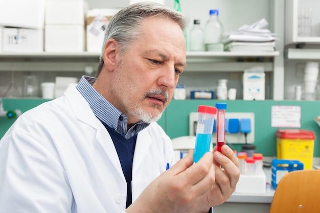 Wissenschaftler, der ein reagenzglas in seinem labor hält