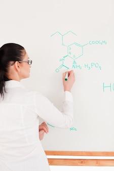 Wissenschaftler, der eine formel auf eine tafel schreibt