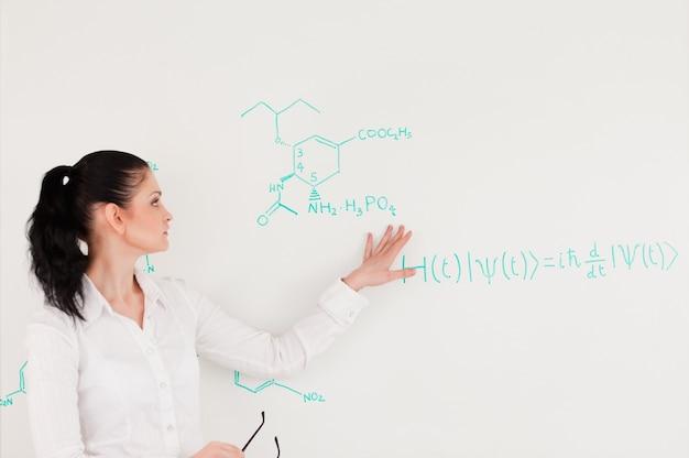 Wissenschaftler, der eine formel geschrieben auf ein weißes brett erklärt