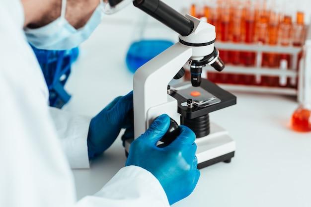Wissenschaftler, der eine kontrollprobe durch ein mikroskop betrachtet