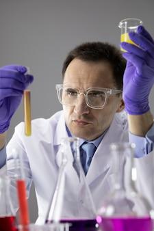 Wissenschaftler, der im labor mit reagenzglasflaschen arbeitet und wissenschaftliche experimente durchführt